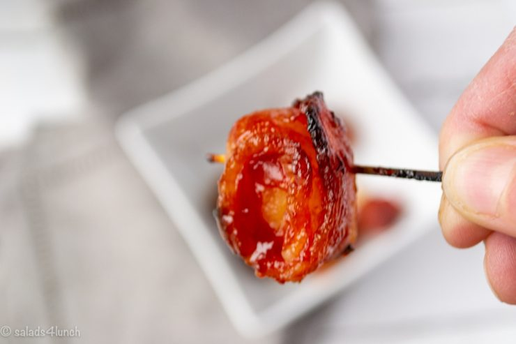 Close up of Bacone Wrapped Water Chestnut on a toothpick in someone's hand.