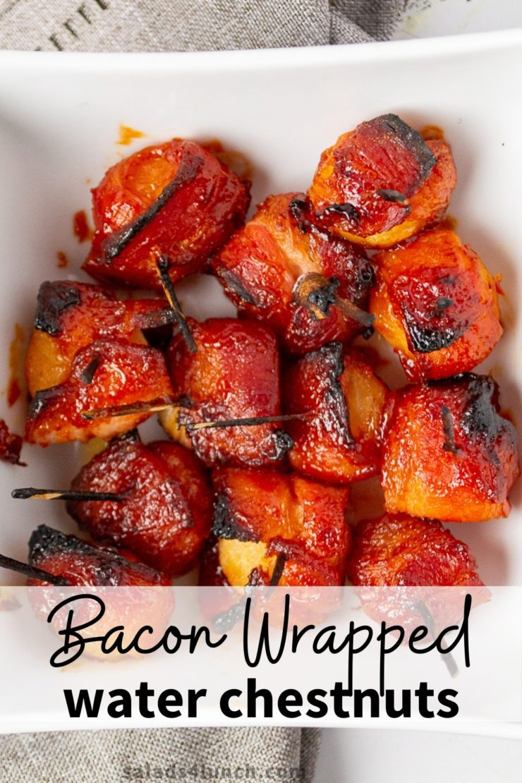 Close up photo of square white bowl full of bacon wrapped water chestnuts appetizerS on a grey napkin.