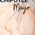 Close up of Chipotle Mayo in white bowl with black rim on a grey napkin with three lime slices in the background.