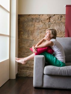Lonely women on grey couch looking out a window