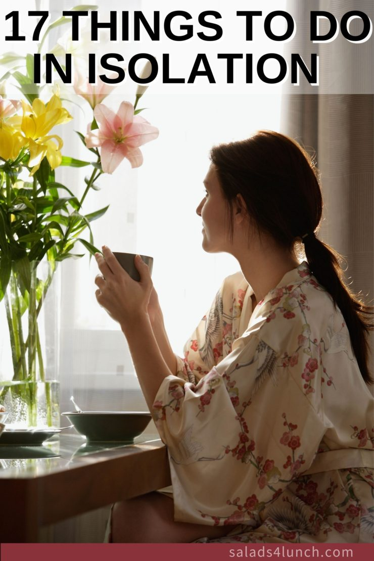 Lonely women holding a tea and wearing a floral robe looking out a window.