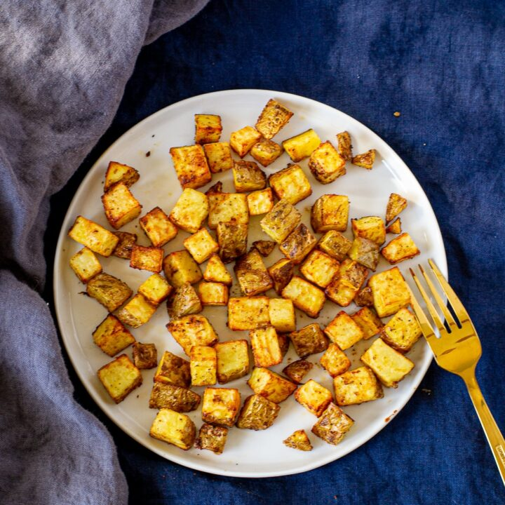 Top view of easy air fried home fries on a white plate on a blue napkin with a gold fork to the right of the plate.