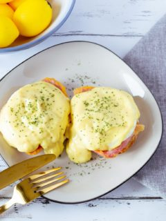 Close up photo of two delicious eggs benedict on a white plate with black trim on a grey napkin with a gold fork and knife.