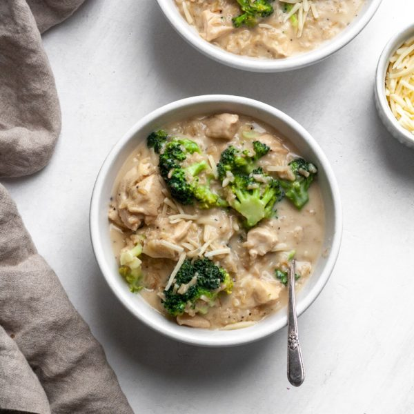 Long photo of chicken broccoli and rice casserole in a white bowl with a tan linen napkin.