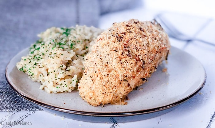 Close up of garlic parmesan baked chicken breast with a side of risotto on a white plate on a grey napkin.