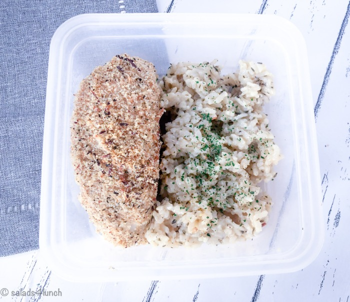 Close up of garlic parmesan baked chicken breast with a side of risotto in a meal storage container on a grey napkin.