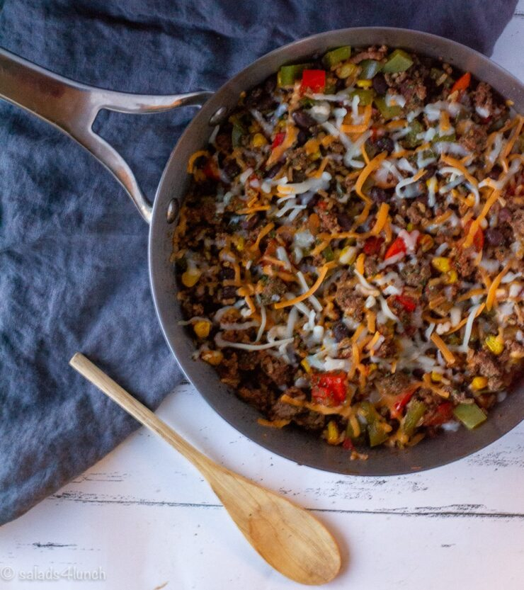 Silver skillet with Mexican Rice Casserole on a blue linen napkin with a wooden spoon to the left of the skillet,