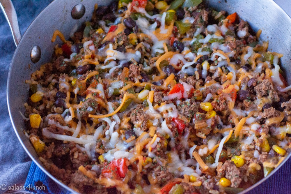 Close up of Mexican Beef and Rice Casserole with black beans and peppers in a skillet.