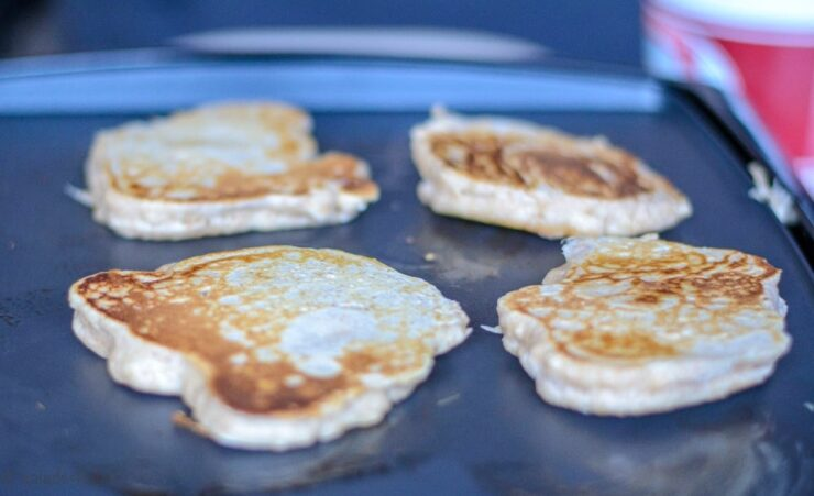 Four fluffy whole wheat pancakes cooking on a griddle.