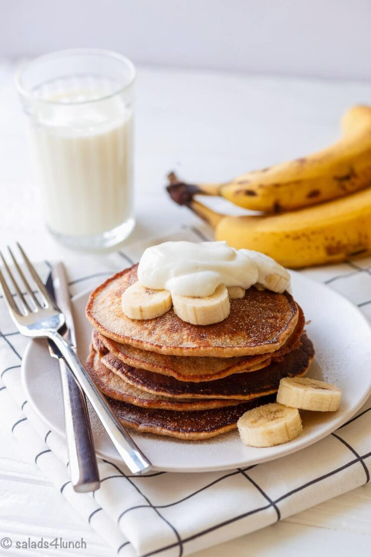 Side view of a stack of four no sugar added whole wheat pancakes on a white plate with a glass of milk and two bananas in the background.