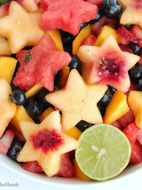 Overhead close up photo of a beautiful fruit salad with watermelon and peaches cut into stars, mango and blueberries in a white bowl.