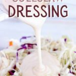 """Creamy Coleslaw dressing being poured over coleslaw in a white bowl with grapes and sunflower seeds with text overlay that says: """"Easy Creamy Coleslaw Dressing""""."""