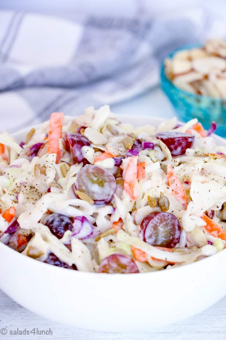 """Creamy Coleslaw in a white bowl with grapes and sunflower seeds with text overlay that says: """"Easy Creamy Coleslaw""""."""
