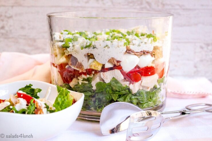 Layered Cobb Salad in a Trifle Bowl on a pink napkin.