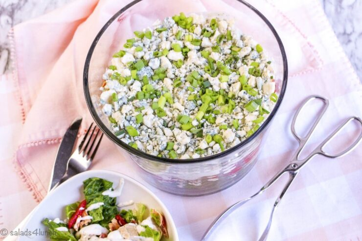 Overhead photo of Cobb Salad in a Trifle Bowl on a peach napkin showing the delicious green onions on the top.