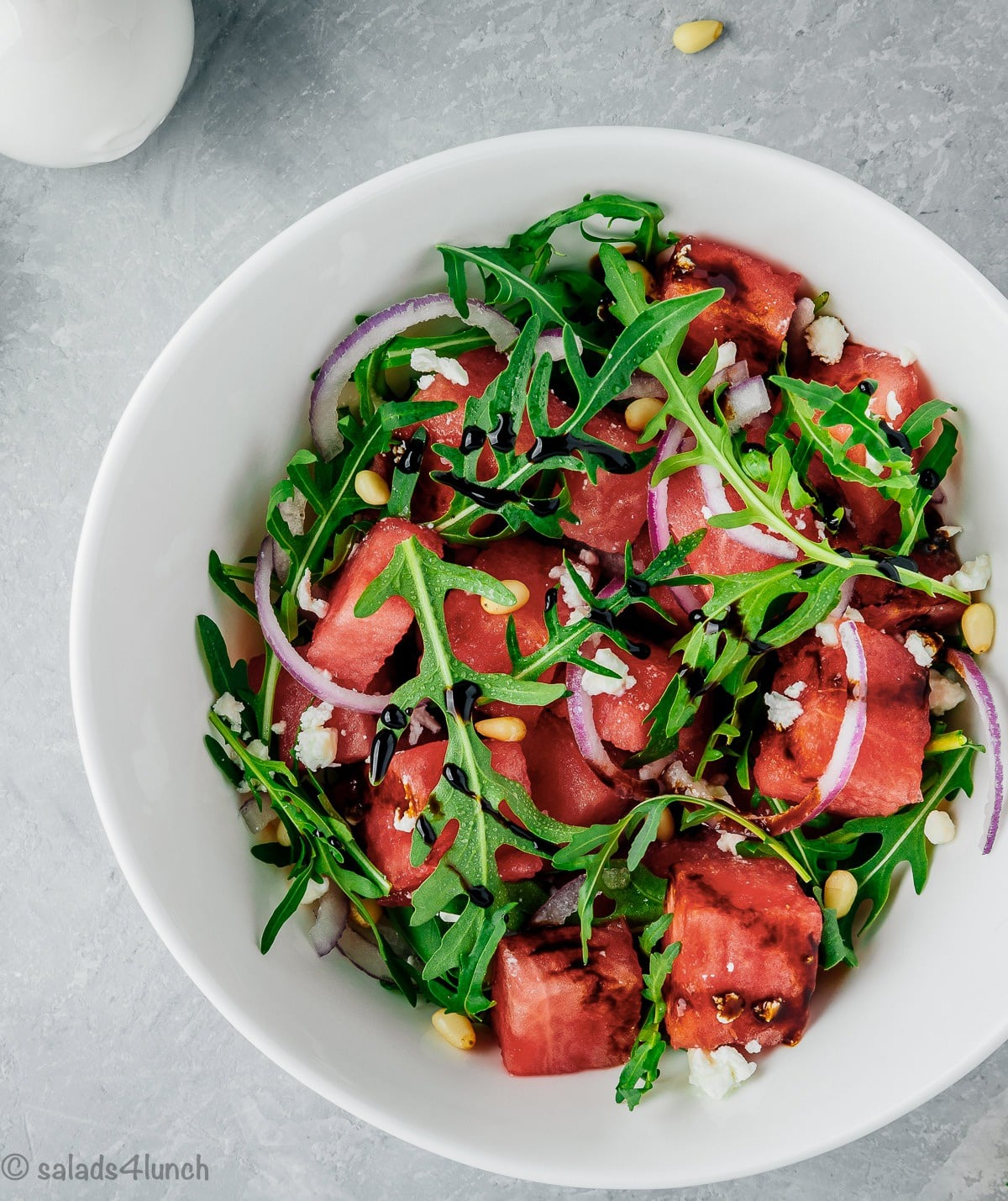 Close up photo of watermelon arugula salad with slivered red onions, feta and pine nuts drizzled with sweet balsamic reduction in a white bowl