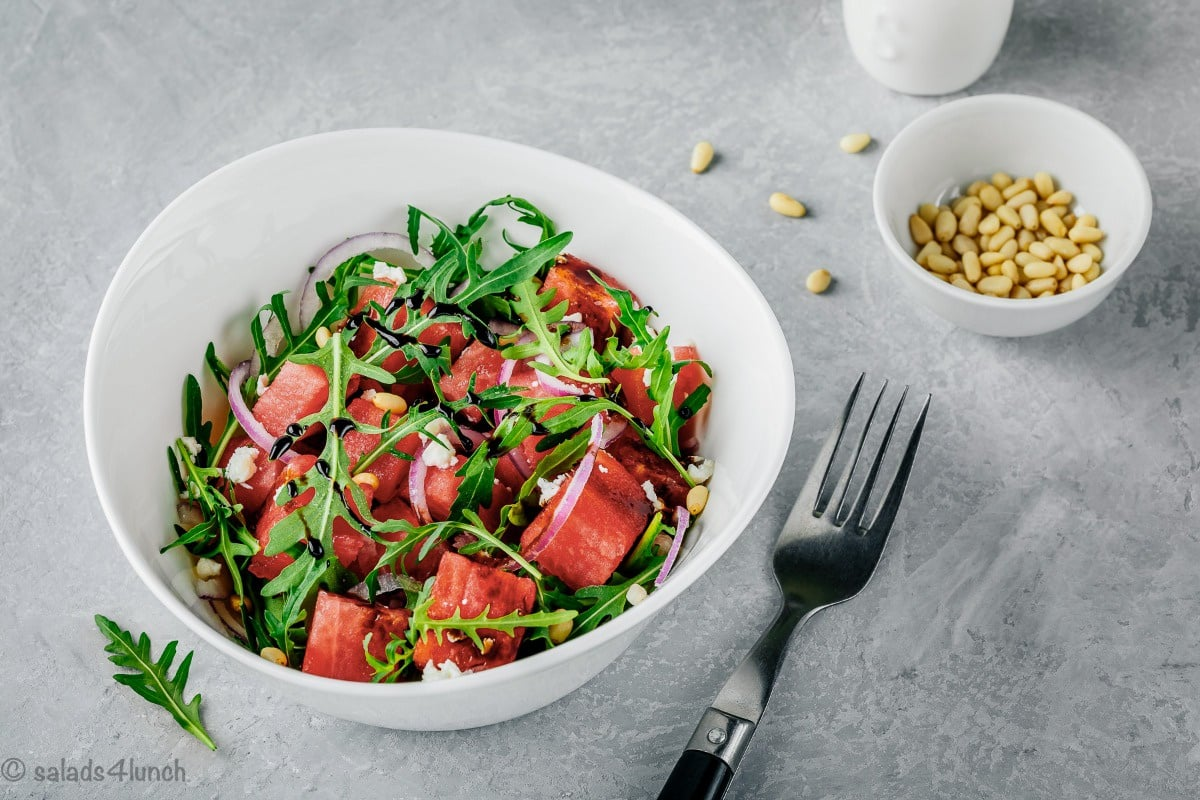 Close up photos of watermelon arugula salad with slivered red onions, feta and pine nuts drizzled with sweet balsamic reduction in a white bowl