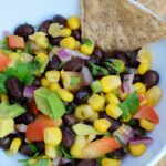 Close up overhead photo of Corn and Black Bean Salsa with Avocado in a white bowl with black bean chips arranged on a plate around the bowl.
