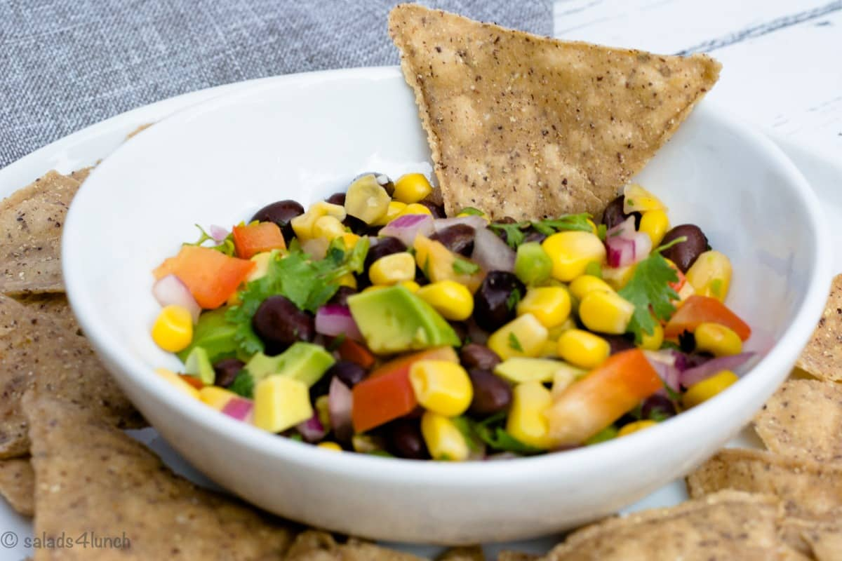 Overhead photo of Corn and Black Bean Salsa in a small white bowl surrounded by black bean chips.